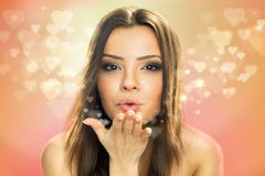 Beautiful woman blowing up kiss with hearts. Picture of beautiful woman blowing hearts, cute female send romantic kiss, Cupid girl, Valentines day, sweet holiday Royalty Free Stock Photos