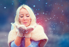 Beautiful woman blowing winter snow  from knitted mittens. Beautiful woman blowing winter snow from knitted mittens Stock Photos