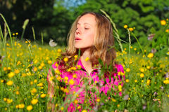 Beautiful woman blows away dandelion Stock Images