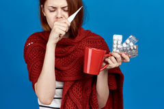 Beautiful woman on a blue background holds a mug, pills, thermometer, sickness, sick, flu Royalty Free Stock Images