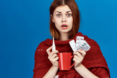 Beautiful woman on blue background, mug, thermometer, pills, flu, sickness, sick, empty space for copy Royalty Free Stock Image