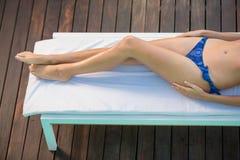 Beautiful woman in blue bikini lying on sun lounger by poolside Stock Images