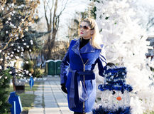 The beautiful woman in a blue coat at a fir-tree and a snowman Royalty Free Stock Photography