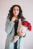 Beautiful woman in blue coat with red roses in craft paper Stock Image