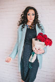 Beautiful woman in blue coat with red roses in craft paper Royalty Free Stock Image