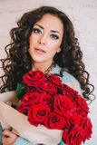 Beautiful woman in blue coat with red roses in craft paper Royalty Free Stock Photo
