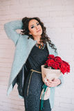 Beautiful woman in blue coat with red roses in craft paper Royalty Free Stock Photography