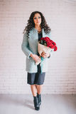 Beautiful woman in blue coat with red roses in craft paper Stock Photography