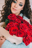 Beautiful woman in blue coat with red roses in craft paper Stock Photos
