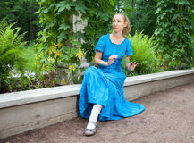 Beautiful woman in a blue dress in the arbor twined a green bindweed Stock Image