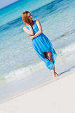 Beautiful woman in blue dress on beach in summer Stock Images