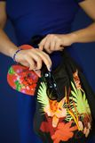 Beautiful woman in blue dress holding beach paraphernalia in her hands, like flip flops, sunglasses and beach bag. Close up picture at her hands, can be used stock image