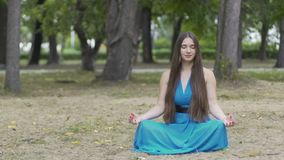 Beautiful woman in blue dress meditates outdoors, place for ad text, dolly shot. Stock footage stock video