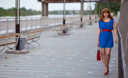 Beautiful woman in blue dress and red shoes Royalty Free Stock Image