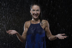 Beautiful woman in blue dress stands in rain at night Royalty Free Stock Photography