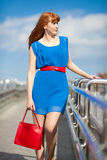 Beautiful woman in blue dress walking Stock Photography
