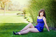 Beautiful woman in a blue dress walks in the park Stock Photos