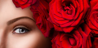 Beautiful woman blue eye with red roses. Close-up of beautiful woman blue eye with red roses Royalty Free Stock Images