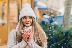 Beautiful woman with blue eyes drinks hot wine on christmas mark Stock Photo