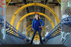 Beautiful woman in blue jeans standing on a bridge. Young girl with boots posing in front of industrial background royalty free stock photos