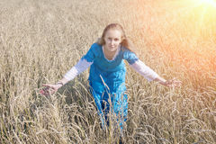 Beautiful woman in a blue long dress in the field of ripe cereals Royalty Free Stock Image