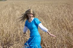 Beautiful woman in a blue long dress in the field of ripe cereals Royalty Free Stock Photo