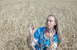 Beautiful woman in a blue long dress in the field of ripe cereals Royalty Free Stock Photography