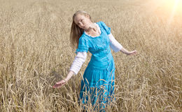 Beautiful woman in a blue long dress in the field of ripe ears of cereals Stock Image