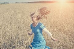 The beautiful woman in a blue long dress in the field of ripe ears of cereals, retro effect Stock Image