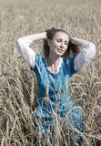 Beautiful woman in a blue long dress in the field of ripe ears of cereals, retro effect Stock Photos