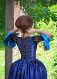 Beautiful woman in blue medieval dress outdoor, back Stock Image