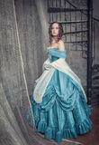 Beautiful woman in blue medieval dress on the stairway Stock Photography