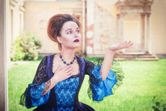 Beautiful woman in blue medieval dress stretching hand to someth Stock Photos