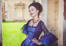 Beautiful woman in blue medieval dress winking Stock Images