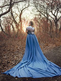 beautiful woman in a blue raincoat royalty free stock photography