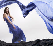 Beautiful woman in blue robes #2. Studio photo beautiful young mysterious girl in a long silk dress color electric blue, standing in an unusual position on a Stock Photography