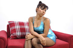 Beautiful woman blue shiny dress on red sofa Stock Image