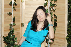 Beautiful woman in blue sits on swing Stock Photography