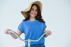 Beautiful woman in blue top and hat holding bicycle Royalty Free Stock Photography