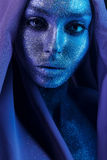 Beautiful woman in blue and violet paint with glitters Royalty Free Stock Image
