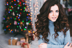 Beautiful woman on a blurry background Christmas decorations. Stock Photos