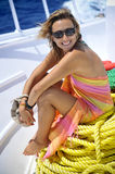 Beautiful woman on boat. An attractive hispanic adult woman with happy smiling facial expression sitting on a rope on a boat Stock Photography