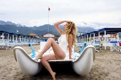 Beautiful Woman in a boat at Forte dei Marmi beach, Italy. Liguria Beautiful mountain view backgrounds. Beautiful Woman in a boat at Forte dei Marmi beach, Italy royalty free stock photos