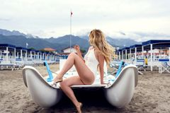 Beautiful Woman in a boat at Forte dei Marmi beach, Italy. Liguria Beautiful mountain view backgrounds. Beautiful Woman in a boat at Forte dei Marmi beach, Italy royalty free stock image