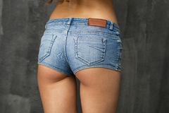 Beautiful woman body in denim jeans shorts. Female body part denim jeans shorts against the dark wall Stock Photo