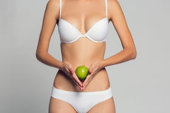 Beautiful woman body and green apple. Conceptual image of dieting healthy lifestyle. Beautiful woman body and green apple. Conceptual image of dieting healthy Stock Photography