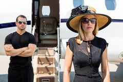 Beautiful Woman With Bodyguard Against Private Jet. Beautiful women wearing sunhat with bodyguard and private jet in background royalty free stock image