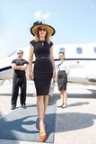 Beautiful Woman With Bodyguard And Airhostess. Full length of beautiful women in elegant dress with bodyguard and airhostess standing against private plane royalty free stock image