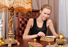 Beautiful woman with book in the antique parlor. Stock Photos