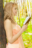 Beautiful woman with book in garden. Sun day Stock Image